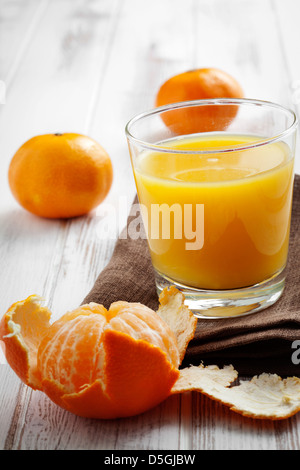 Glass of orange juice with some tangerines - Stock Photo