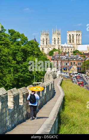 York Minster and tourist walking along a section of the historic city walls Station road York Yorkshire England - Stock Photo