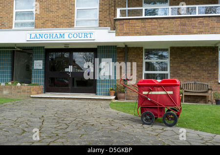 A british postman's trolley outside a block of flats whilst the postman delivers mail inside. - Stock Photo