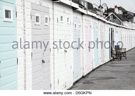 Candy coloured beach huts on the sea front at Lyme Regis, Dorset in winter - Stock Photo