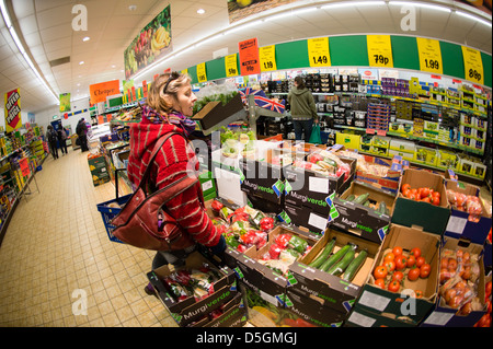 A middle aged woman shopping for fresh vegetables and other food in LIDL discount supermarket, UK - Stock Photo