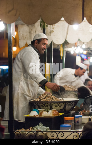 Man selling snails from a stall in the Djemaa el-Fna square at night, Marrakech, Morocco - Stock Photo