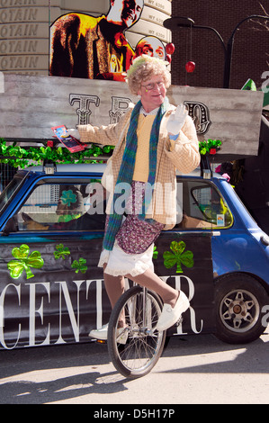 Male unicyclist dressed up as an elderly woman at the St Patricks Day parade in Montreal, province of Quebec, Canada. - Stock Photo