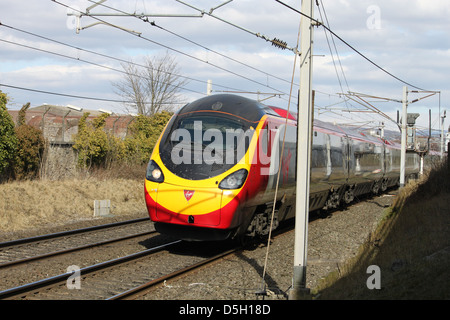 Class 390 Pendolino electric train on West Coast Main line approaching Carnforth with a southbound train operated - Stock Photo