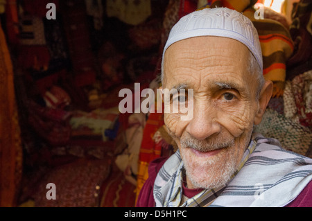 Old Moroccan man working at a stall in the souk, Marrakech, Morocco - Stock Photo