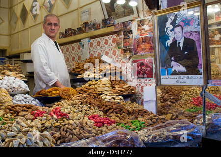 Man selling sweets and pastries at a stall in the souk, with a portrait of the King, Marrakech, Morocco - Stock Photo