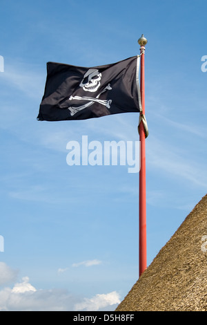 jolly roger pirate flag with a skull and crossbones on a blue sky background - Stock Photo