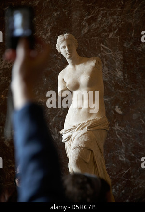 Venus de Milo, Aphrodite statue in the Louvre with a tourist 's arm and hand taking a photograph - Stock Photo