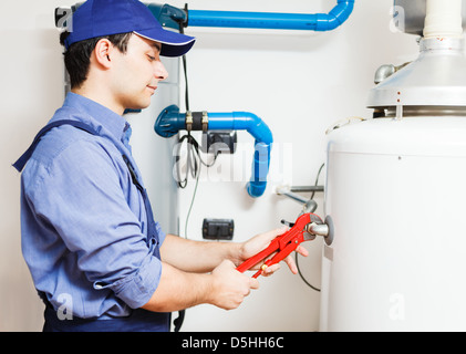 Plumber repairing an hot-water heater - Stock Photo