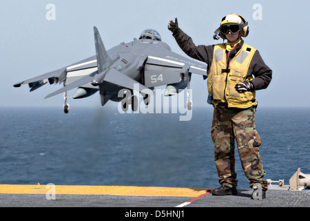 A US Navy Aviation Boatswain's Mate signals as an AV-8B Harrier fighter jet takes off from the amphibious assault - Stock Photo