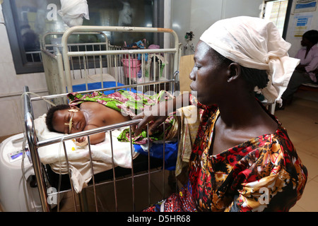 Mother watches her sick baby in a hospital in Techiman, Ghana - Stock Photo