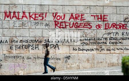 A man walks past a graffiti covered wall in Athens, Greece, 19 September 2012. Photo: Maurizio Gambarini - Stock Photo