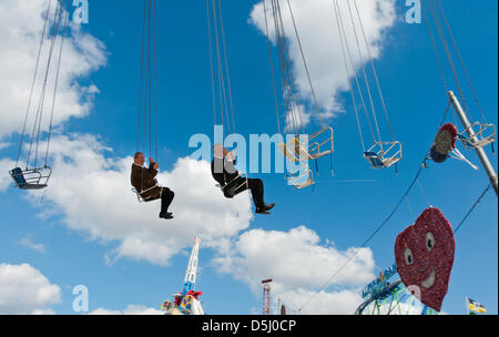 Munich Mayor Christian Ude (L) and Oktoberfest director Dieter Reiter take a ride on a flying swing during a tour - Stock Photo