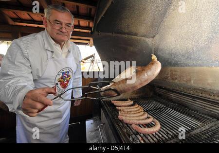 Ingolf Stellmacher grills traditionally produced German bratwurst (fried sausage) in Holzhausen, Germany, 14 November - Stock Photo
