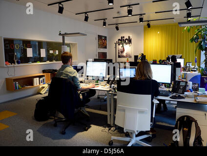 Employees work at their desks in Google's Berlin office in Germany, 13 November 2012. The office opened recently - Stock Photo