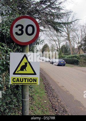 30 mph speed limit sign and sign warning of cats crossing on a road in rural England. - Stock Photo