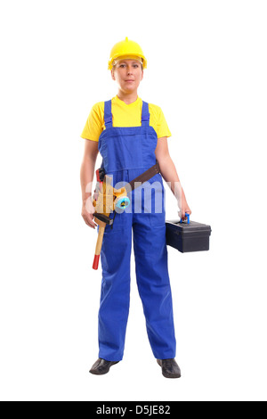 Service woman in blue overall  and yellow helmet wearing leather toolbelt with tools, holding black toolbox over - Stock Photo