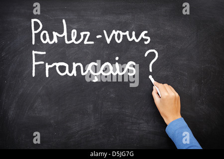 Teacher or student writing parlez-vous francais (do you speak French) on blackboard. Learning French language concept - Stock Photo