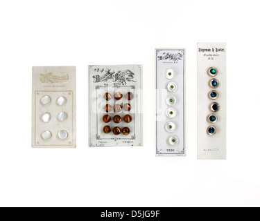 Antique button cards with mother-of-pearl and glass buttons on a white background. - Stock Photo