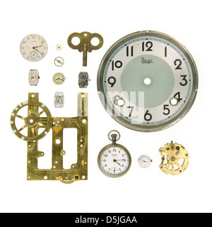 Clock parts, clock faces, and watch mechanisms on a white background - Stock Photo