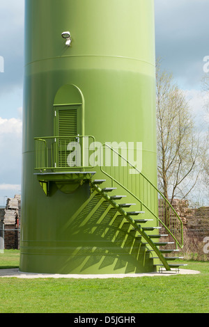 Base of green wind turbine with stairs en entrance doorfor workmen, operators and technicians. - Stock Photo