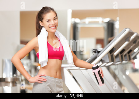 Portrait of happy smiling young multicultural fit woman with towel standing by treadmills in fitness club - Stock Photo