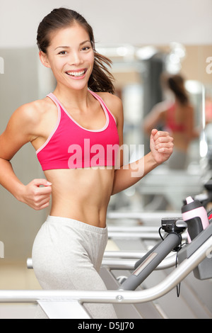 Beautiful smiling young mixed race Chinese Asian and Caucasian woman running on treadmill in gym - Stock Photo