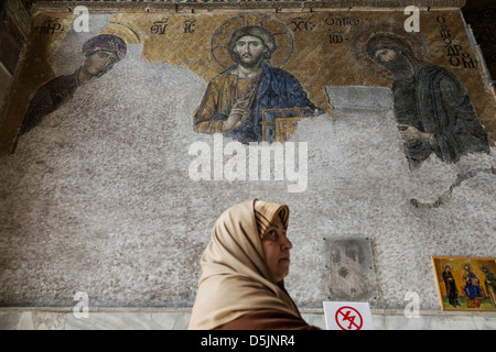 Islamic woman in front of The Deesis mosaic with Christ as ruler - Stock Photo
