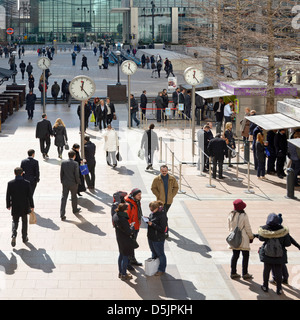 Office workers at lunchtime on Canary Wharf plaza with clocks London Docklands Isle of Dogs Tower Hamlets East London - Stock Photo