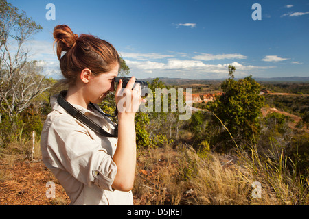 Madagascar, Ambanja, female tourist taking picture at viewpoint overlooking Mozambique Channel - Stock Photo