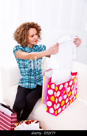 Attractive young woman in her home after a day of shopping, looking at the clothes she bought - Stock Photo