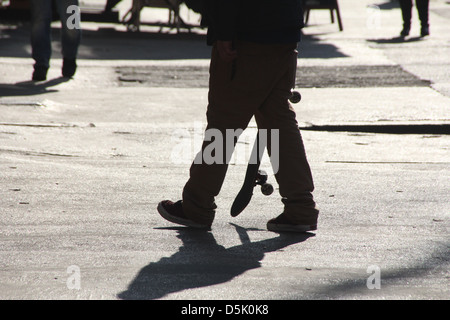 man with skateboard on street road in city town - Stock Photo