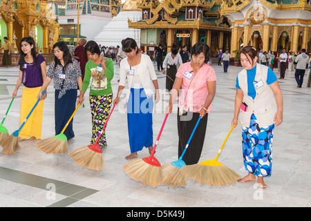 Women sweeping tiled floor at Shwedagon Pagoda, Yangon (Rangoon), Myanmar, (Burma) - Stock Photo