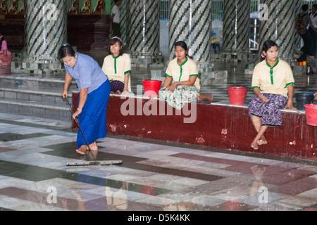 Woman cleaning tiled floor at Shwedagon Pagoda, Yangon (Rangoon), Myanmar, (Burma) - Stock Photo
