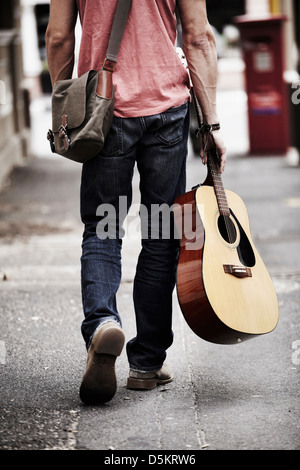 Man with guitar walking down street - Stock Photo