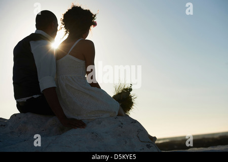 Newlywed couple looking at setting sun - Stock Photo
