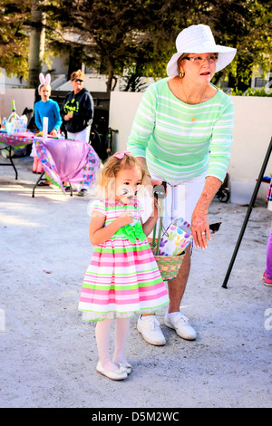 Young girl wearing bunny ears and her face painted takes part in the annual Siesta Key Village FL Easter Egg hunt - Stock Photo