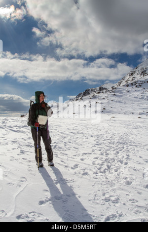 Female hill walker person taking in breathtaking views heading towards Bowfell from Rosset Pike - Stock Photo