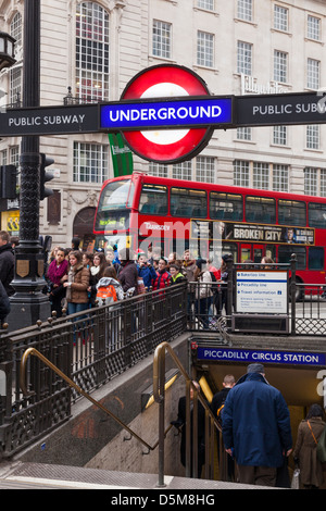 Piccadilly Circus Underground station entrance and London red bus. - Stock Photo