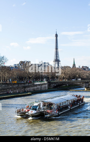 Tourist boat on Seine River viewed from Pont Alexandre III (Alexandre III Bridge) and Eiffel Tower in the background. - Stock Photo