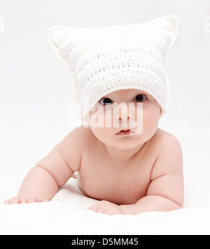 baby in white hat lies on bed - Stock Photo