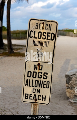Signs at South Beach, Miami, FL, USA, announcing beach closure times and a ban on dogs. - Stock Photo