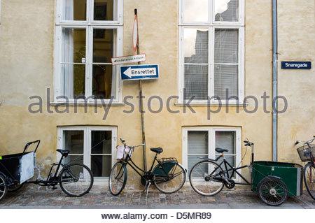 Bikes lined up against a wall on a sidewalk in central Copenhagen, Region Hovedstaden, Denmark - Stock Photo