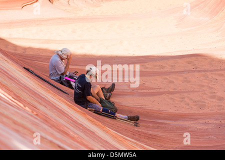 Resting hikers after reaching The Wave - colorful sandstone rock formation located - Stock Photo