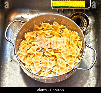Freshly boiled Farfalle, or bow tie, pasta draining in colander in kitchen sink with bright yellow sponge. - Stock Photo