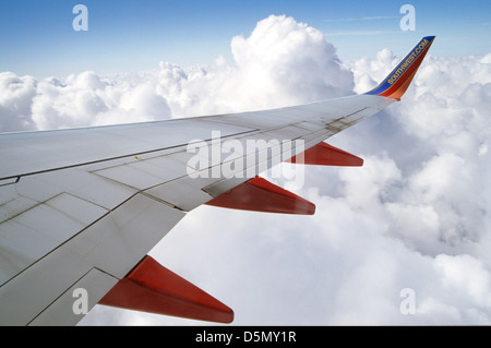 view out window of Southwest Airlines wing and clouds - Stock Photo