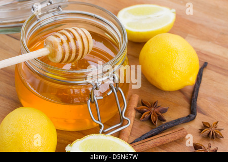 glass honey jar, spices and lemons on wooden table - Stock Photo