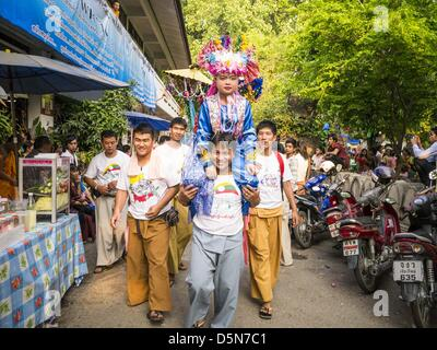 Chiang Mai, Thailand. 5th April 2013. A boy is are carried through the grounds of Wat Pa Pao during the Poi Sang - Stock Photo