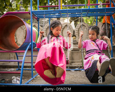 Chiang Mai, Thailand. 5th April 2013. Thai girls in traditional clothes play on a swing set at Wat Pa Pao. Their - Stock Photo