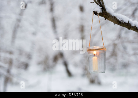 Christmas candle in a glass jar in a snow covered wood - Stock Photo